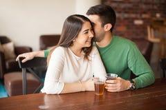 Man whispering to a girl at the bar Stock Photos