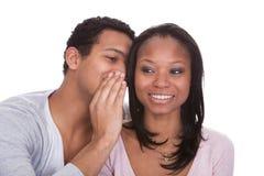 Man whispering to girlfriend's ear Stock Photos