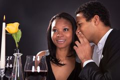 Man whispering to girlfriend's ear. Portrait Of Man Whispering To Girlfriend's Ear At Dinner Royalty Free Stock Images