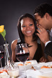 Man Whispering To Girlfriend's Ear. Portrait Of Man Whispering To Girlfriend's Ear At Dinner Stock Photography