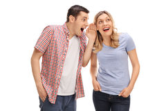 Man whispering to his female friend. Man whispering something to his female friend and both laughing isolated on white background Stock Image
