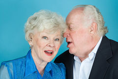 Man whispering to wife Royalty Free Stock Images