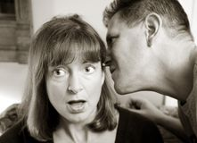 Man whispering to woman Royalty Free Stock Photo