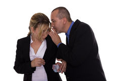 Man whispering to woman. Man puts money in womans pocket Stock Photo