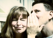 Man whispering in woman's ear Stock Images