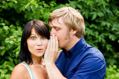 Man whispering into the woman's ear Royalty Free Stock Photography