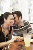 Man Whispering In Woman's Ears At Sidewalk Cafe Royalty Free Stock Photography