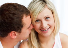 Man whispering a woman something funny. Close-up of a man whispering a woman something funny royalty free stock photo
