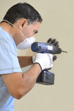 Man whit drill. Caucasian workman with protective mask working with a drill Royalty Free Stock Images