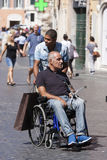 Man whit wheelchair and black man assistant Royalty Free Stock Photos