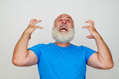 Man with white beard is infuriated and nervous. Isolated against white background Royalty Free Stock Photo