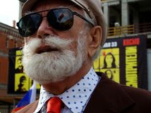 Man with a white beard wearing sunglasses and a hat. Street