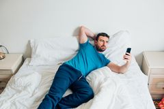Man portrait on white bed using smartphone Royalty Free Stock Photography
