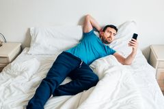 Man portrait on white bed using smartphone Stock Photo