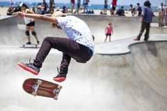 Man in White and Black Floral Shirt Riding on Brown and Red Skateboard Stock Photo