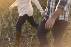 Man in White Blue and Black Plaid Dress Shirt Blue Jeans Holding Hand With Girl in White Sweater Blue Jeans and Brown Leather Boot Royalty Free Stock Images