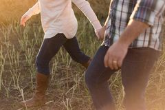 Man in White Blue and Black Plaid Dress Shirt Blue Jeans Holding Hand With Girl in White Sweater Blue Jeans and Brown Leather Boot Royalty Free Stock Photos