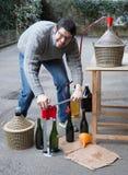 Man white bottling red wine from the demijohn. To glass bottles Stock Photos