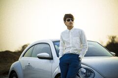 Man in White Button Down Shirt Leaning on Silver Beetle Car Royalty Free Stock Photo