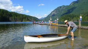 Man with a White Canoe at Buntzen Lake Park. Buntzen Lake Park in Anmore, BC, Canada. People are fishing and canoeing royalty free stock images