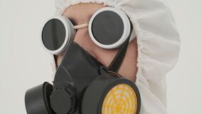 Man in white chemical protection suite. Head in respirator close up