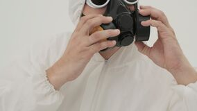 Man in white chemical protection suite puts a respirator on himself