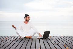 Man in white clothes meditating yoga with laptop on wooden pier Stock Image