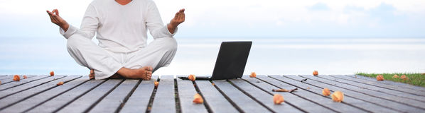 Man in white clothes meditating yoga with laptop on wooden pier Stock Images