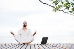 Man in white clothes meditating yoga with laptop on wooden pier Stock Photography