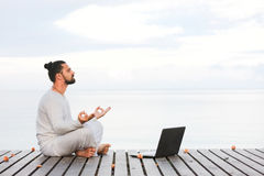 Man in white clothes meditating yoga with laptop on wooden pier Stock Photos