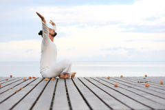 Man in white clothes meditating yoga with laptop on wooden pier Royalty Free Stock Photo