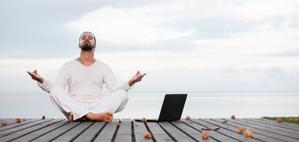 Man in white clothes meditating yoga with laptop on wooden pier Royalty Free Stock Photos