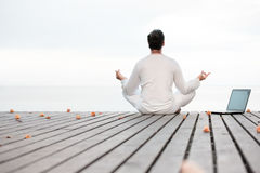 Man in white clothes meditating yoga with laptop on wooden pier Royalty Free Stock Photography