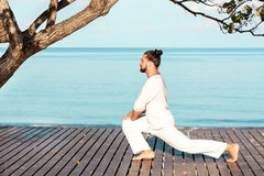 Man in white clothes meditating yoga on wooden pier Royalty Free Stock Photography