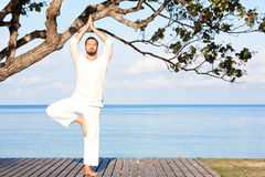 Man in white clothes meditating yoga on wooden pier Royalty Free Stock Images