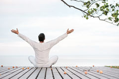 Man in white clothes meditating yoga on wooden pier Stock Photo