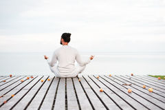 Man in white clothes meditating yoga on wooden pier platform Royalty Free Stock Photos