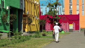 Man in white clothes walks down the street with manycoloured buildings. Man in white clothes walks down the street with many-coloured buildings stock footage