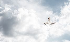 Young man keeping mind conscious. Man in white clothing keeping eyes closed and looking concentrated while meditating on clouds in the air with cloudy skyscape Royalty Free Stock Photo