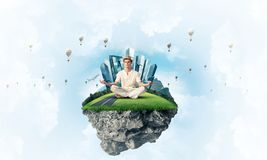 Young man keeping mind conscious. Man in white clothing keeping eyes closed and looking concentrated while meditating on flying island with cloudy skyscape and Stock Photography