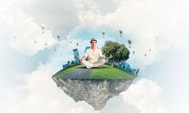 Young man keeping mind conscious. Man in white clothing keeping eyes closed and looking concentrated while meditating on flying island with cloudy skyscape and Royalty Free Stock Image