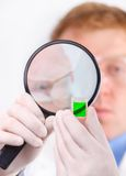 Man in white coat looking at a green sample Royalty Free Stock Photography