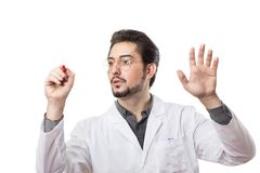 A man in a white coat with a red marker on a transparent glass. White background Stock Photos