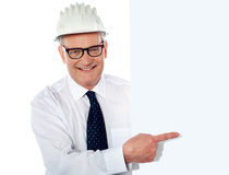 Man in white construction helmet holding placard Stock Photos