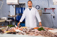 Man in white cover-slut showing fish on counter Stock Photo