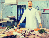 Man in white cover-slut showing fish on counter Royalty Free Stock Images
