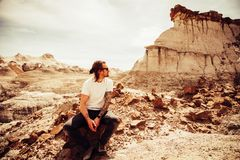 Man in White Crew-neck T-shirt and Black Pants Sitting on Boulder Near Cliff stock photo