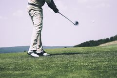 Man in White Denim Pants and Black Sandals Playing Golf during Daytime Stock Image