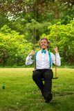 Man in White Dress Shirt and Black Pants Sitting on Swing Stock Photo