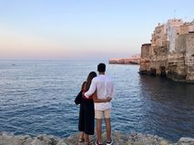 Man in White Dress Shirt Standing Beside the Woman in Black and Red Dress While Watching the Blue Calm Water Near Brown Concrete B stock photos